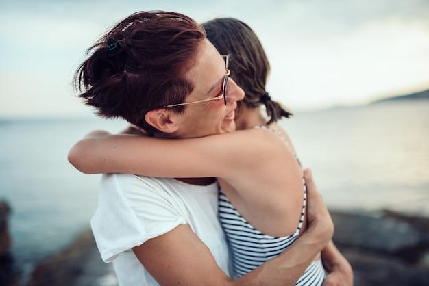 Mãe e filha abraçando na praia