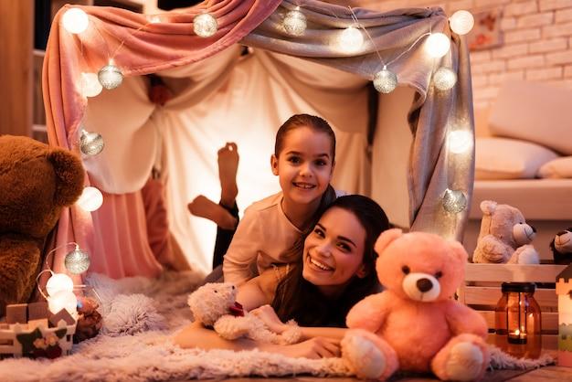 Mãe e filha, abraçando-se na casa de almofadas.