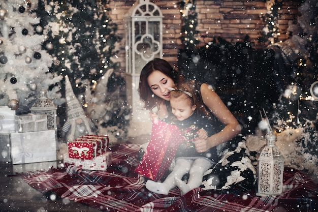 Mãe e filha, abrindo o presente de natal