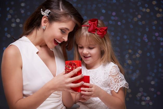 Mãe e filha abrindo presente juntas