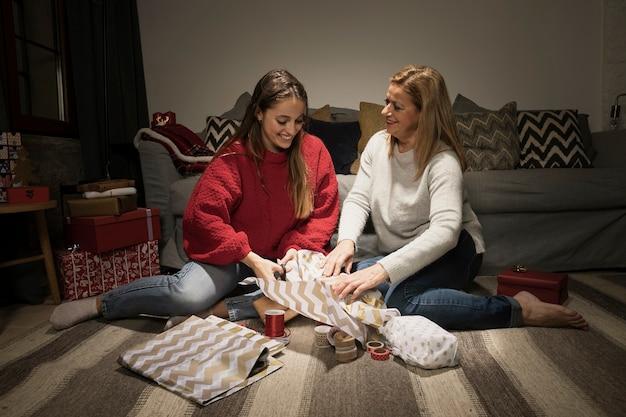 Mãe e filha abrindo presentes