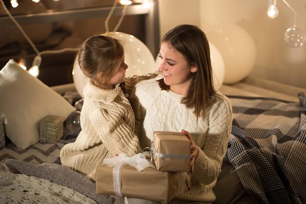 Mãe e filha abrindo um presente de natal mágico no interior aconchegante