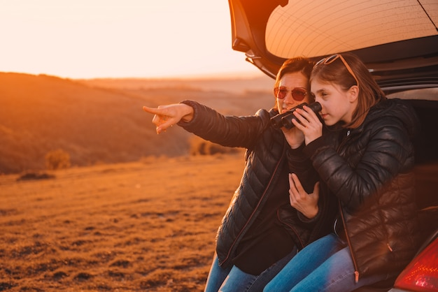 Mãe e filha acampar na colina e usando binóculos