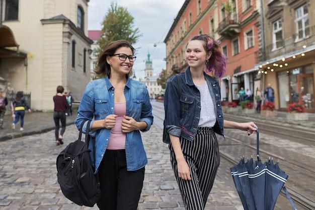 Mãe e filha adolescente andando na rua da cidade