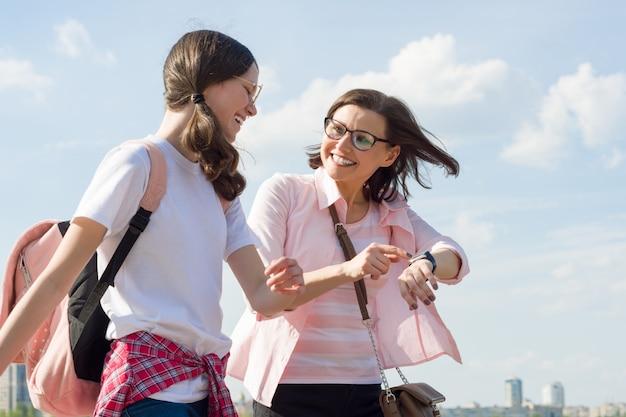 Mãe e filha adolescente andando pela rua da cidade.
