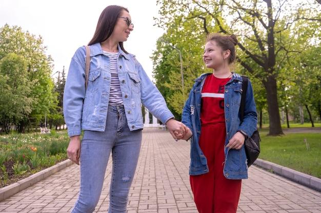 Mãe e filha adolescente caminhando em um parque, de mãos dadas, uma jovem feliz mulher caucasiana com cabelo comprido e uma adolescente andando em uma cidade, estilo de vida familiar