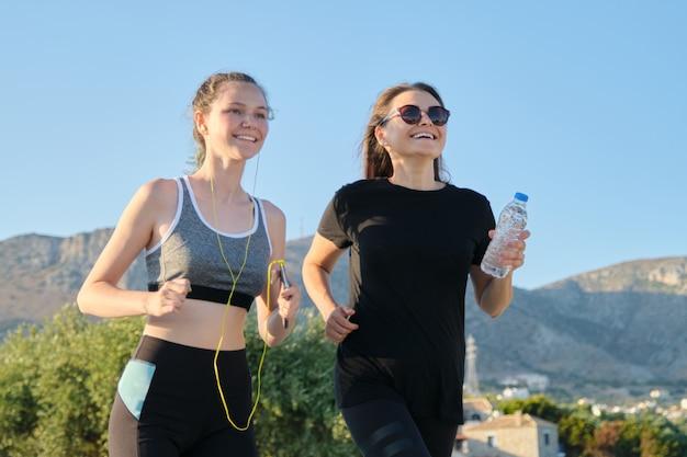Mãe e filha adolescente correndo ao ar livre