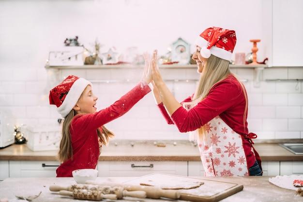 Mãe e filha adolescente estão brincando na cozinha com farinha