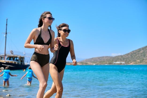 Mãe e filha adolescente juntas na praia, correndo pelo mar em traje de banho. férias em família, amizade e comunicação entre pais e adolescente. férias de verão, mar, estilo de vida, lazer, família