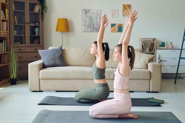 Mãe e filha adolescente sentadas em colchonetes e praticando ioga em casa