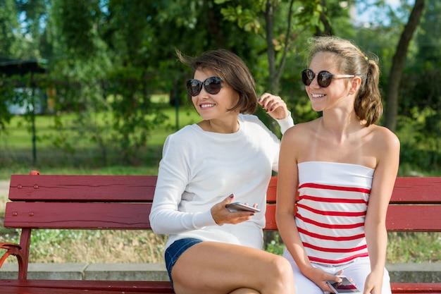 Mãe e filha adolescente sentado no banco