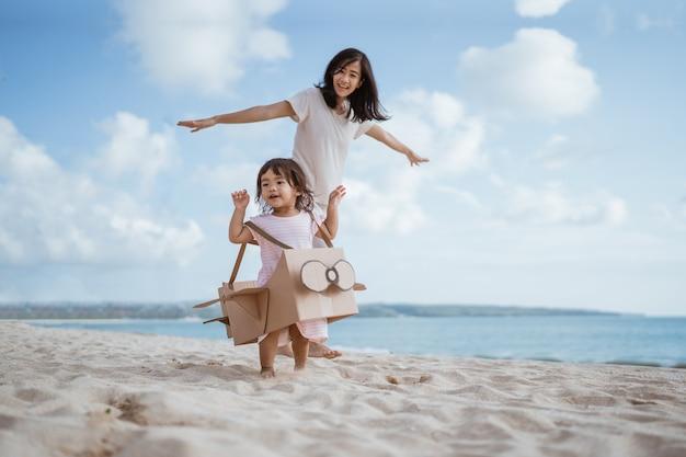 Mãe e filha adoráveis brincando com um brinquedo de papelão de avião