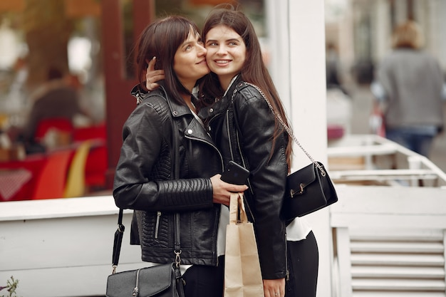 Mãe e filha adulta com sacola de compras