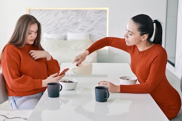 Mãe e filha adulta comem cereal matinal em casa ou na mesa de jantar