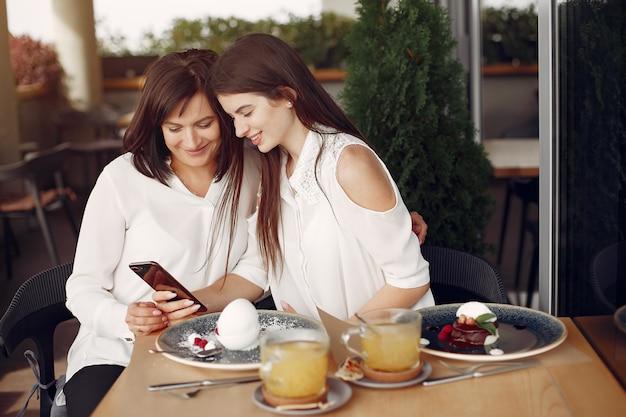 Mãe e filha adulta, sentado em um café