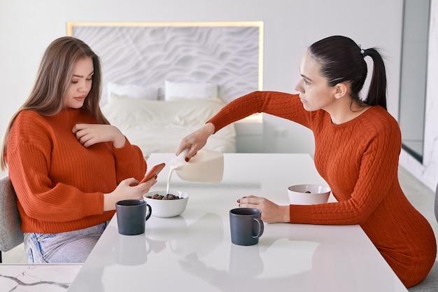 Mãe e filha adulta, vestidas de vermelho, comem cereal matinal com leite.