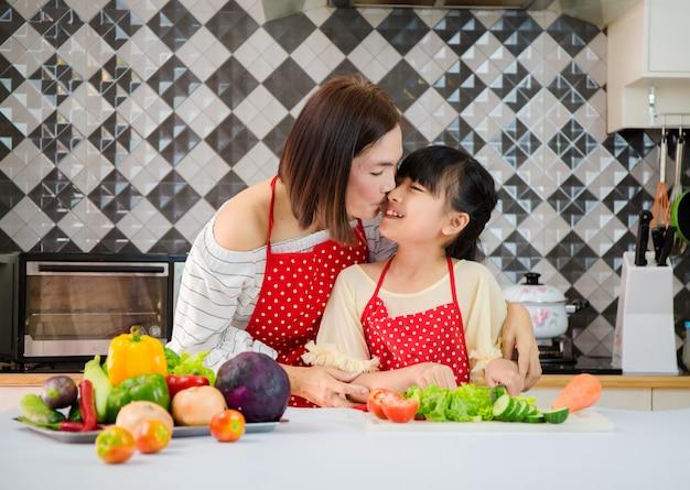 Mãe e filha ajudam a preparar legumes com na cozinha. conceito de família feliz