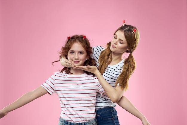 Mãe e filha alegres com camisas listradas