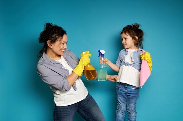Mãe e filha alegres com roupas idênticas seguram um spray de limpeza enquanto brincam com detergentes