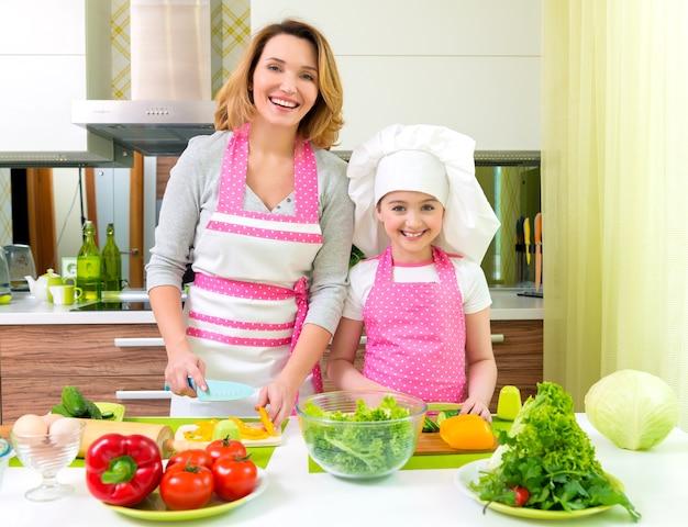 Mãe e filha alegres e sorridentes a cozinhar uma salada na cozinha