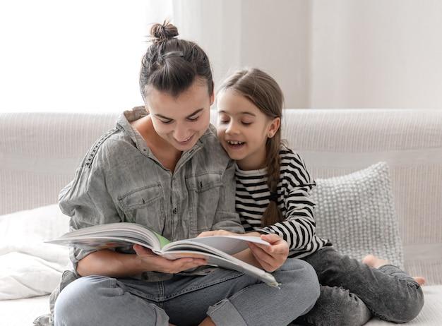 Mãe e filha alegres estão descansando em casa, lendo um livro juntas