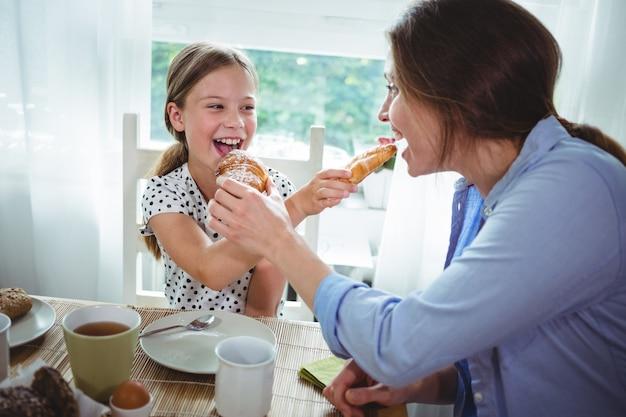 Mãe e filha alimentando croissant um ao outro enquanto tomando café da manhã