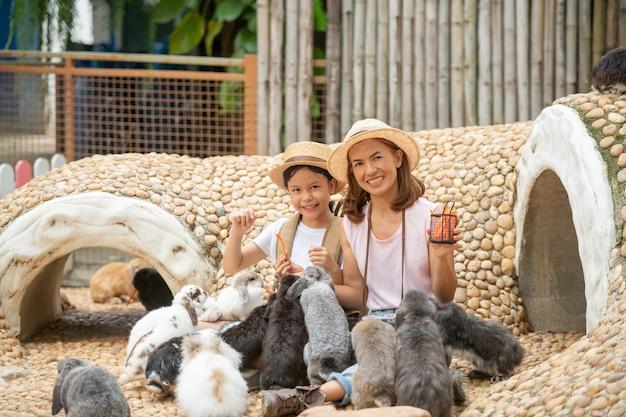 Mãe e filha alimentando e acariciando o coelhinho.