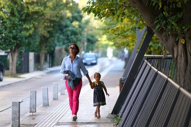 Mãe e filha andam pela cidade