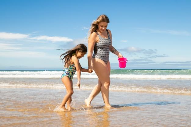 Mãe e filha andando até os tornozelos na água do mar e na areia molhada, pegando conchas no balde