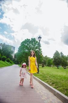 Mãe e filha andando em um caminho com paralelepípedos