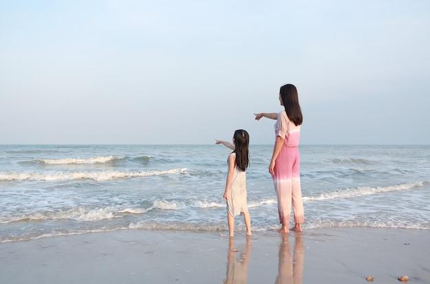 Mãe e filha apontando algo olhando para o mar