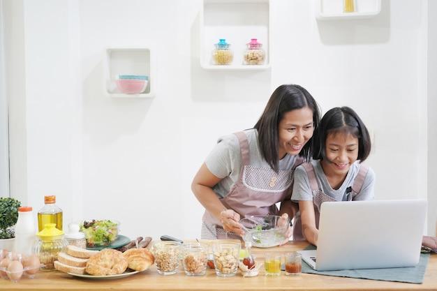 Mãe e filha aprendem cozinhar usando o computador portátil na cozinha em casa