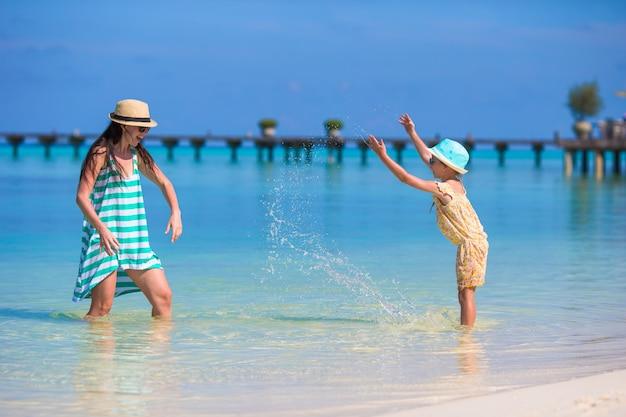 Mãe e filha, aproveitando o tempo na praia tropical