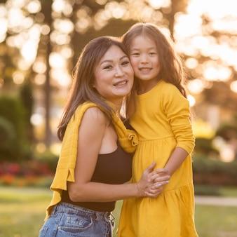 Mãe e filha asiática de mãos dadas