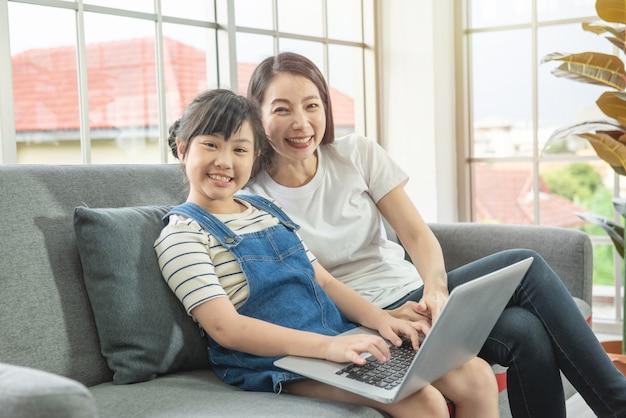 Mãe e filha asiática olhando para a câmera com um sorriso sentado no sofá, descansando, usando um laptop online