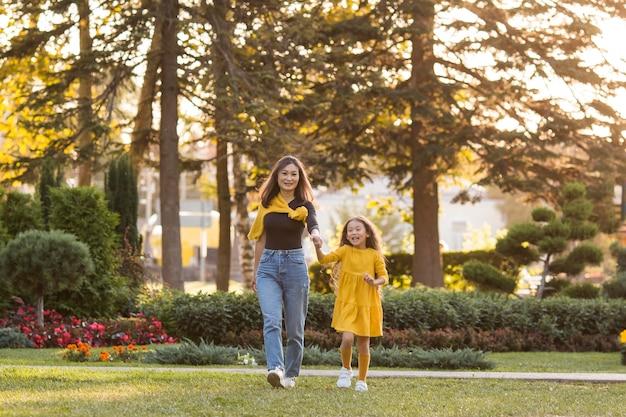 Mãe e filha asiática passeando no parque