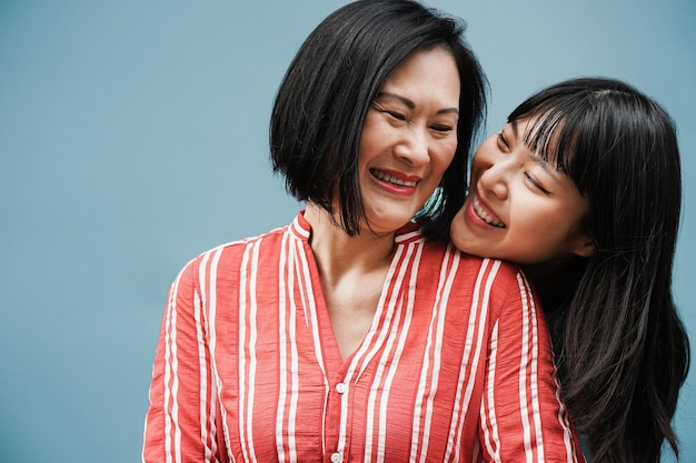 Mãe e filha asiática se abraçando ao ar livre com fundo azul