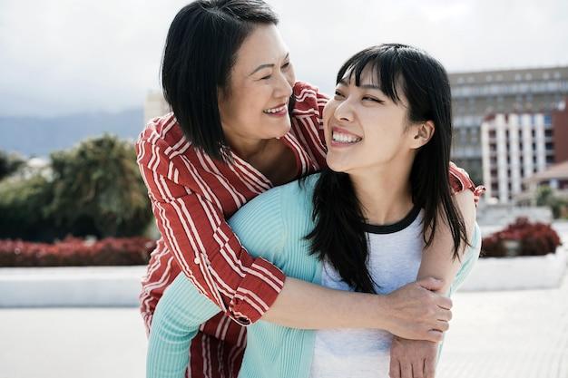 Mãe e filha asiática se divertindo ao ar livre na cidade - foco principal no rosto da menina