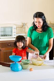 Mãe e filha asiáticas em casa na cozinha