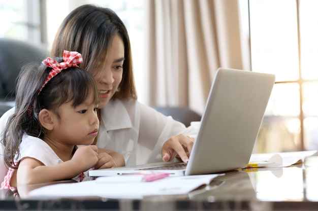 Mãe e filha asiáticas em casa