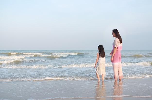 Mãe e filha asiáticas na praia do mar de férias
