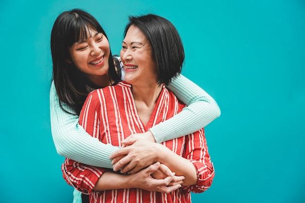 Mãe e filha asiáticas se divertindo ao ar livre - família feliz que aprecia o tempo juntos - amor, estilo de vida dos pais, conceito de momentos delicados - foco nos rostos