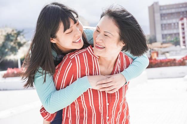 Mãe e filha asiáticas se divertindo ao ar livre