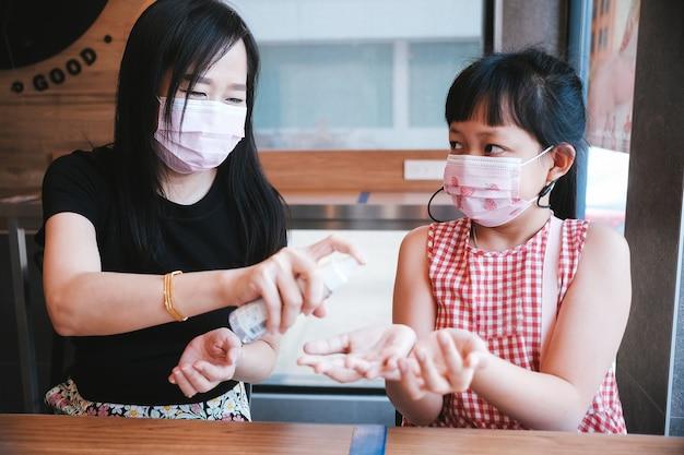Mãe e filha asiáticas usando máscara usando álcool em spray para prevenir o covid-19
