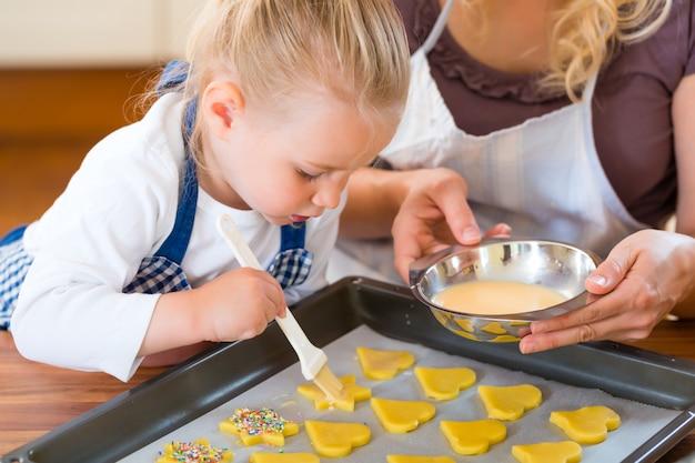 Mãe e filha assando biscoitos juntos