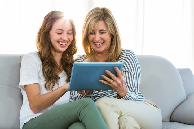 Mãe e filha assistem tablet em casa