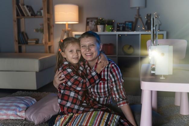 Mãe e filha assistindo a um filme antigo em um projetor de filmes retrô vintage em casa