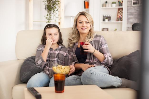 Mãe e filha assistindo a um filme sentadas no sofá em um dia de preguiça, comendo batatinhas e bebendo refrigerante.