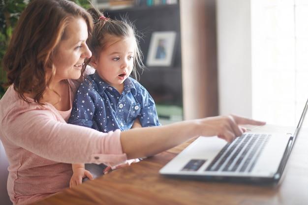 Mãe e filha assistindo vídeo em um laptop