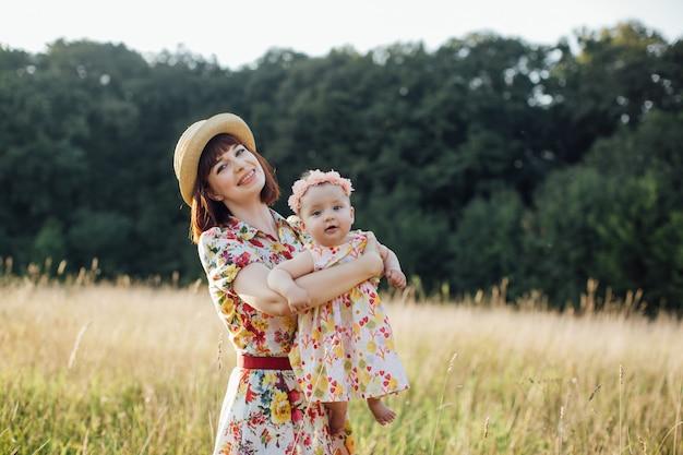 Mãe e filha bebê em vestidos elegantes, se divertindo e girando no campo ao pôr do sol. conceito de dia das mães. passeio de verão com bebê